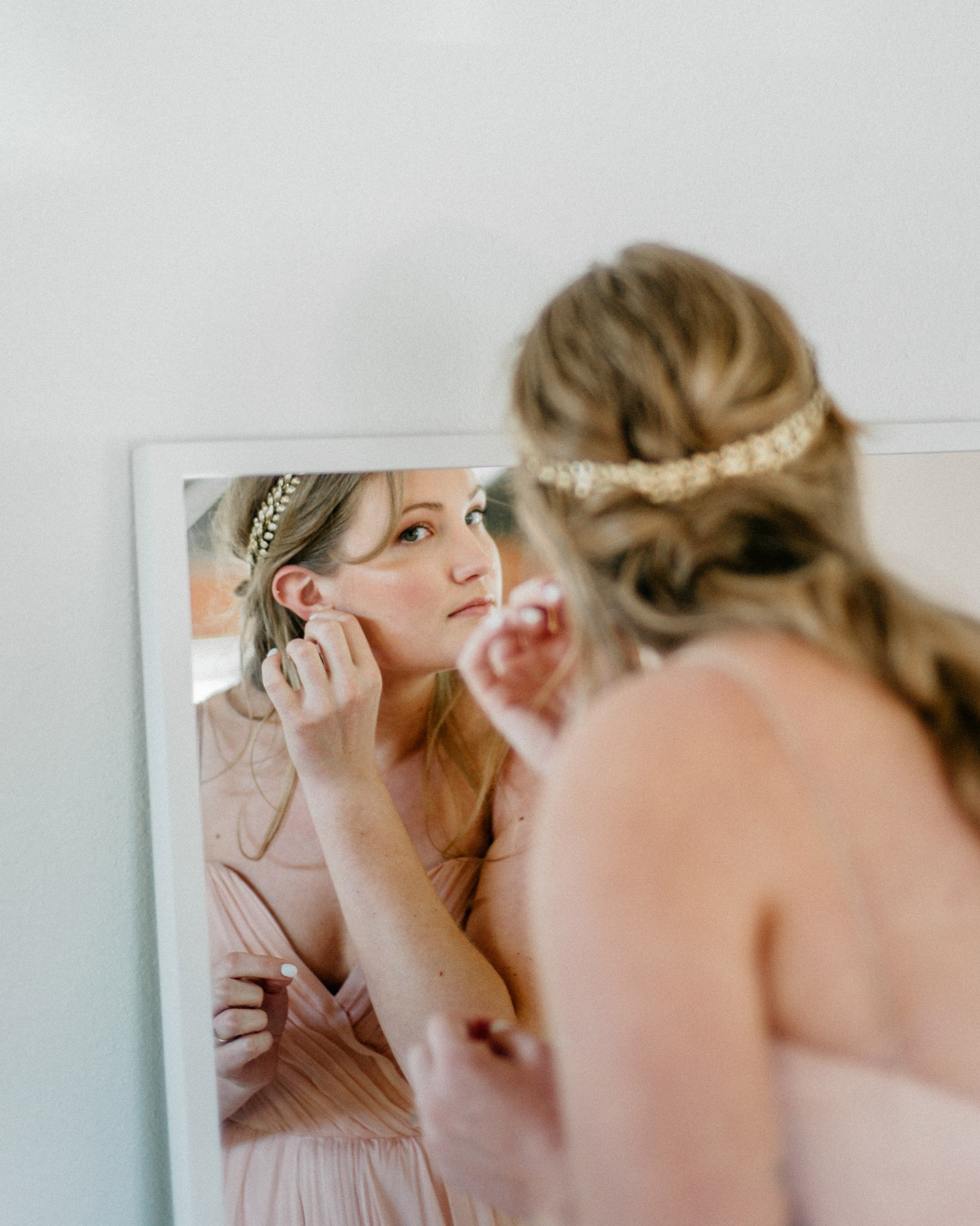 bride putting on her earrings in pink dress
