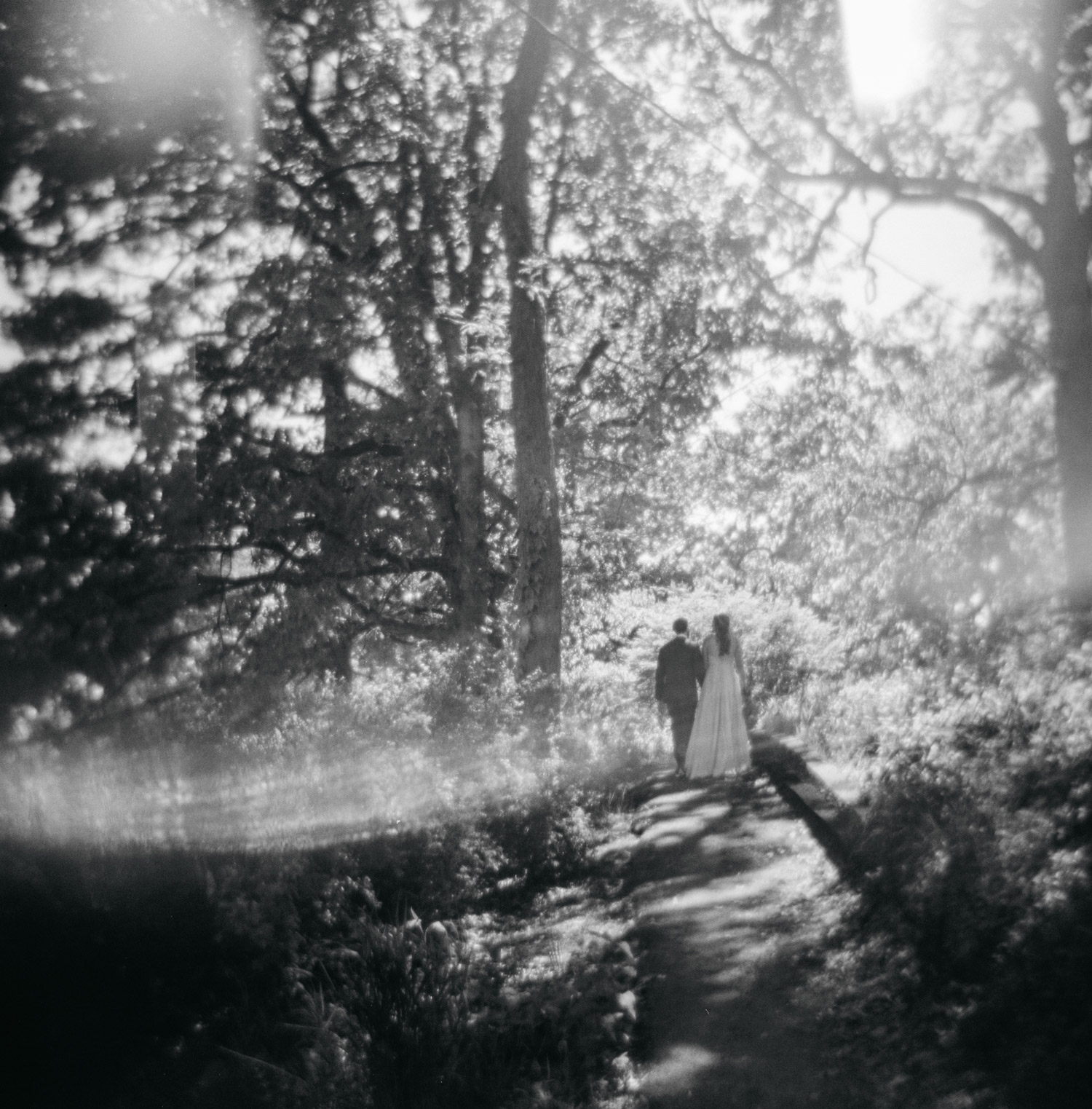 Holga film portrait of bride and groom walking through forest