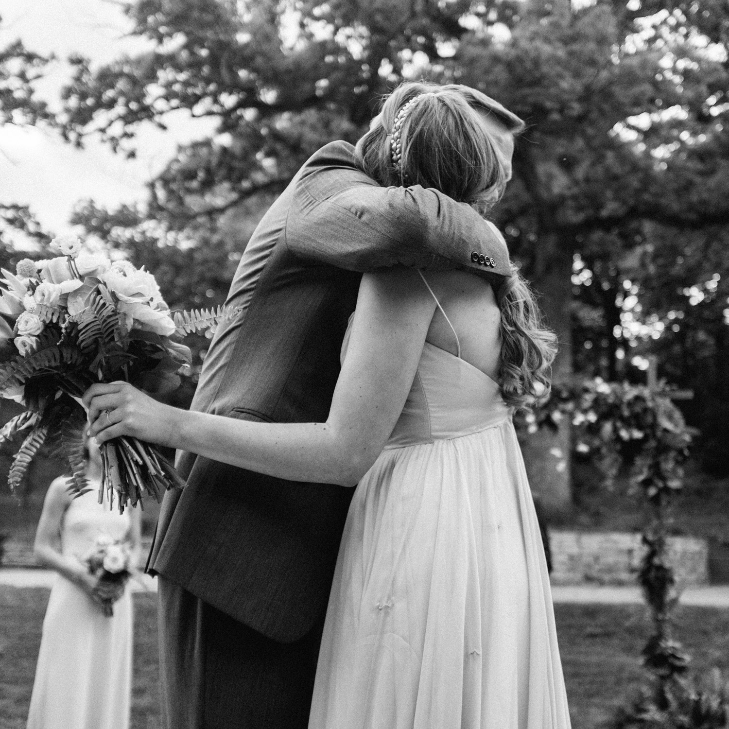 Bride hugs her father during their outdoor ceremony at the Des Moines Art Center