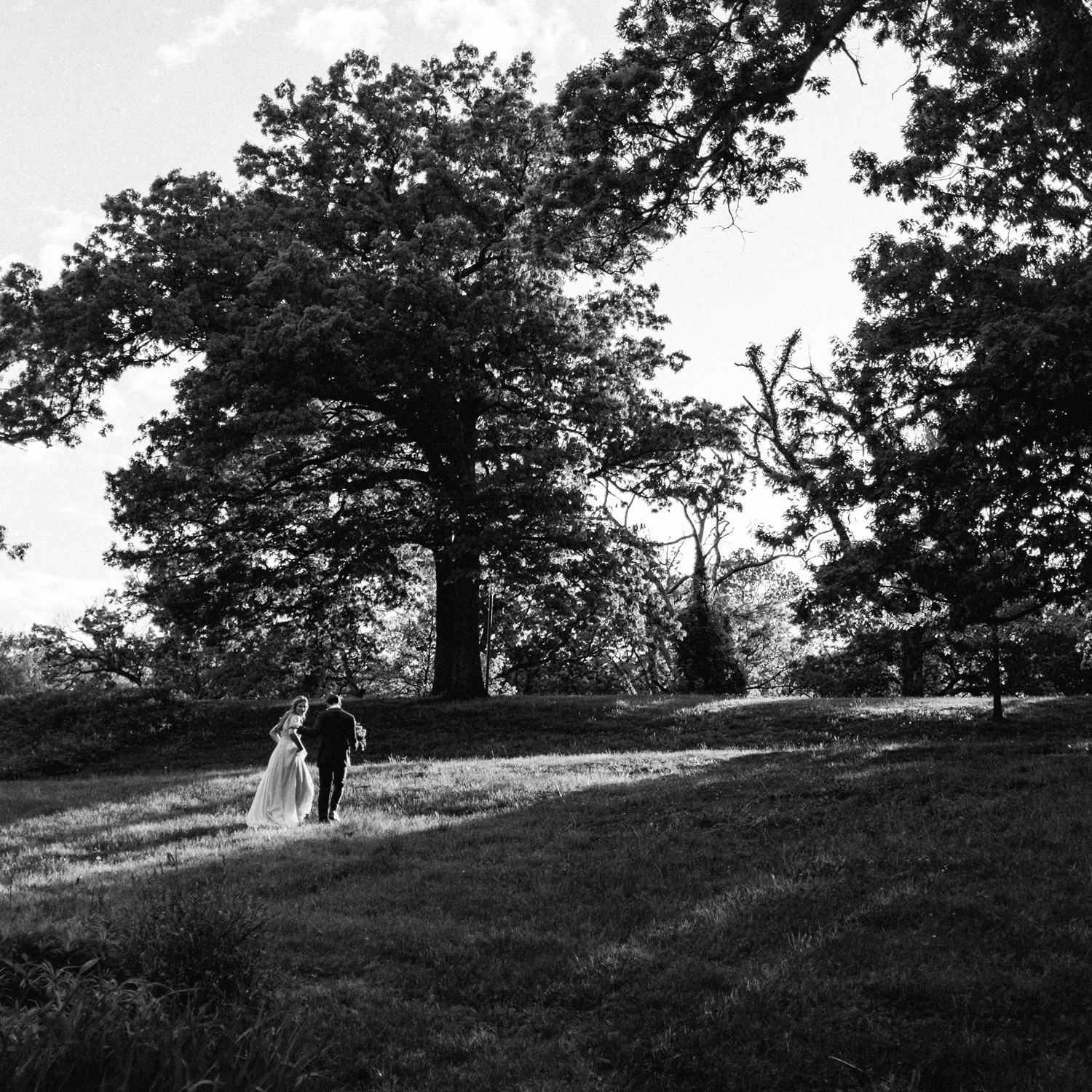 portrait of bride and groom walking together in the sunlight
