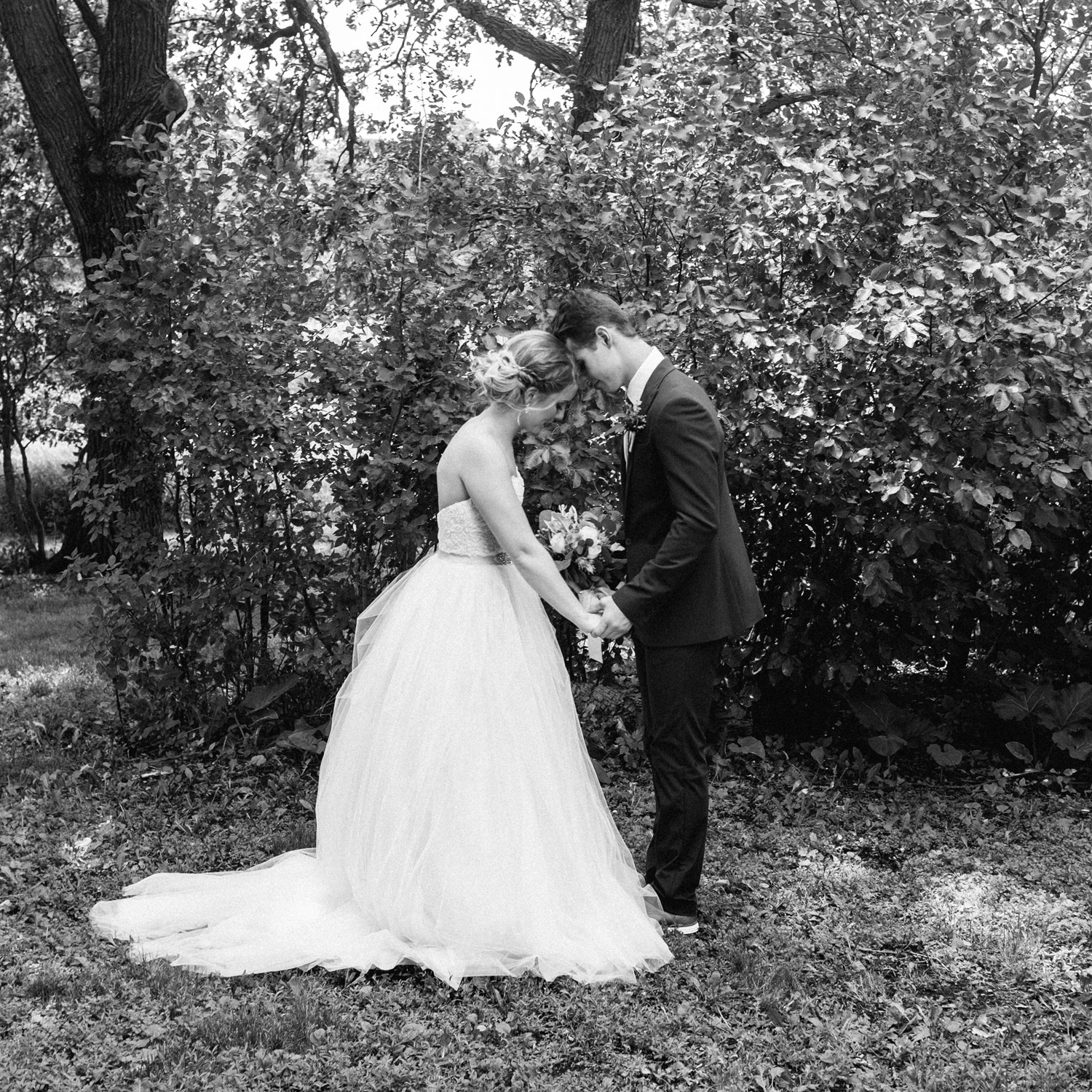bride and groom pray together during first look by geneoh photography