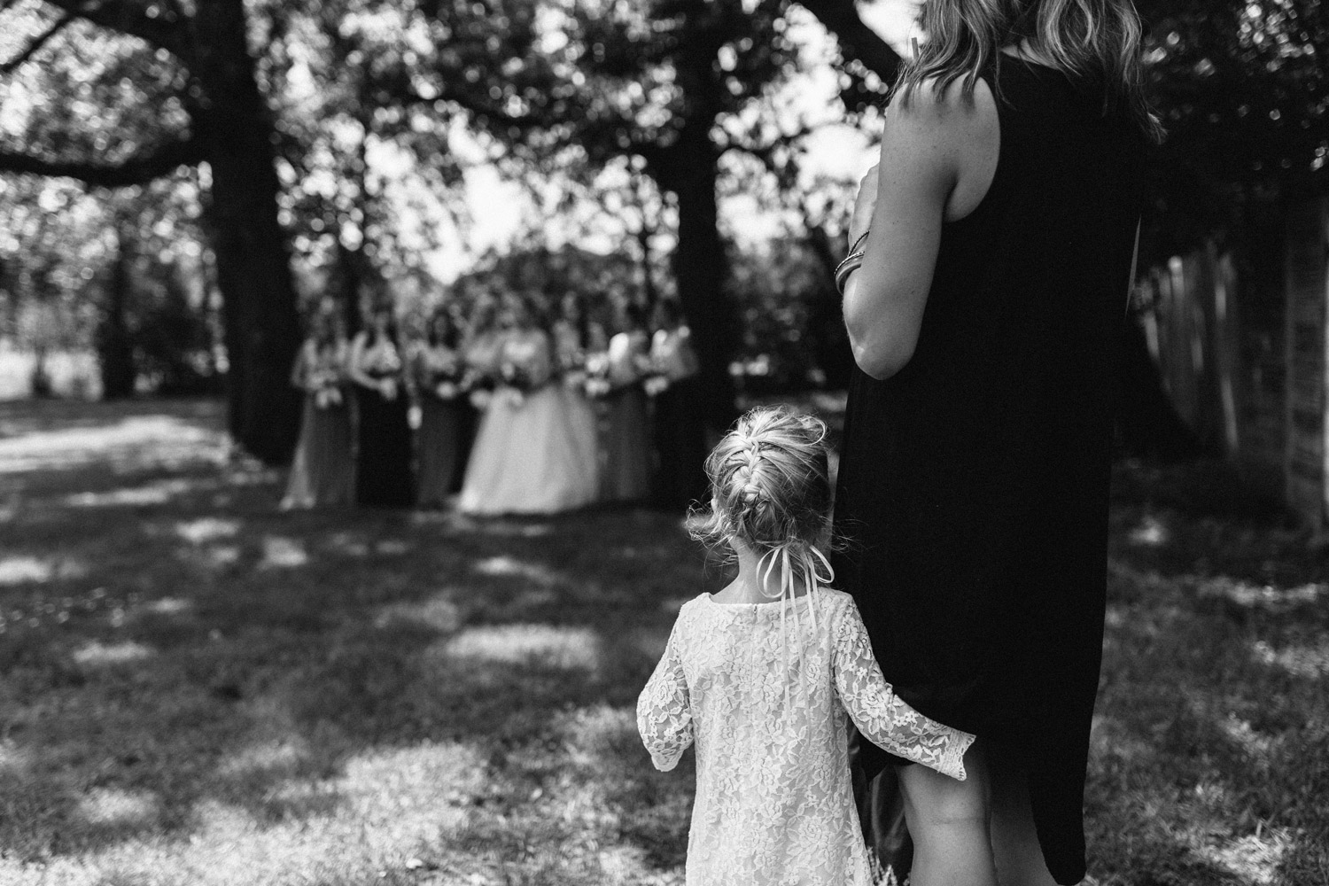 flower girl watching bridesmaids candid at rustic oaks