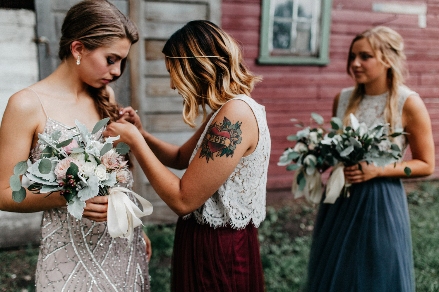 candid of bridesmaids getting ready for portraits at rustic oaks