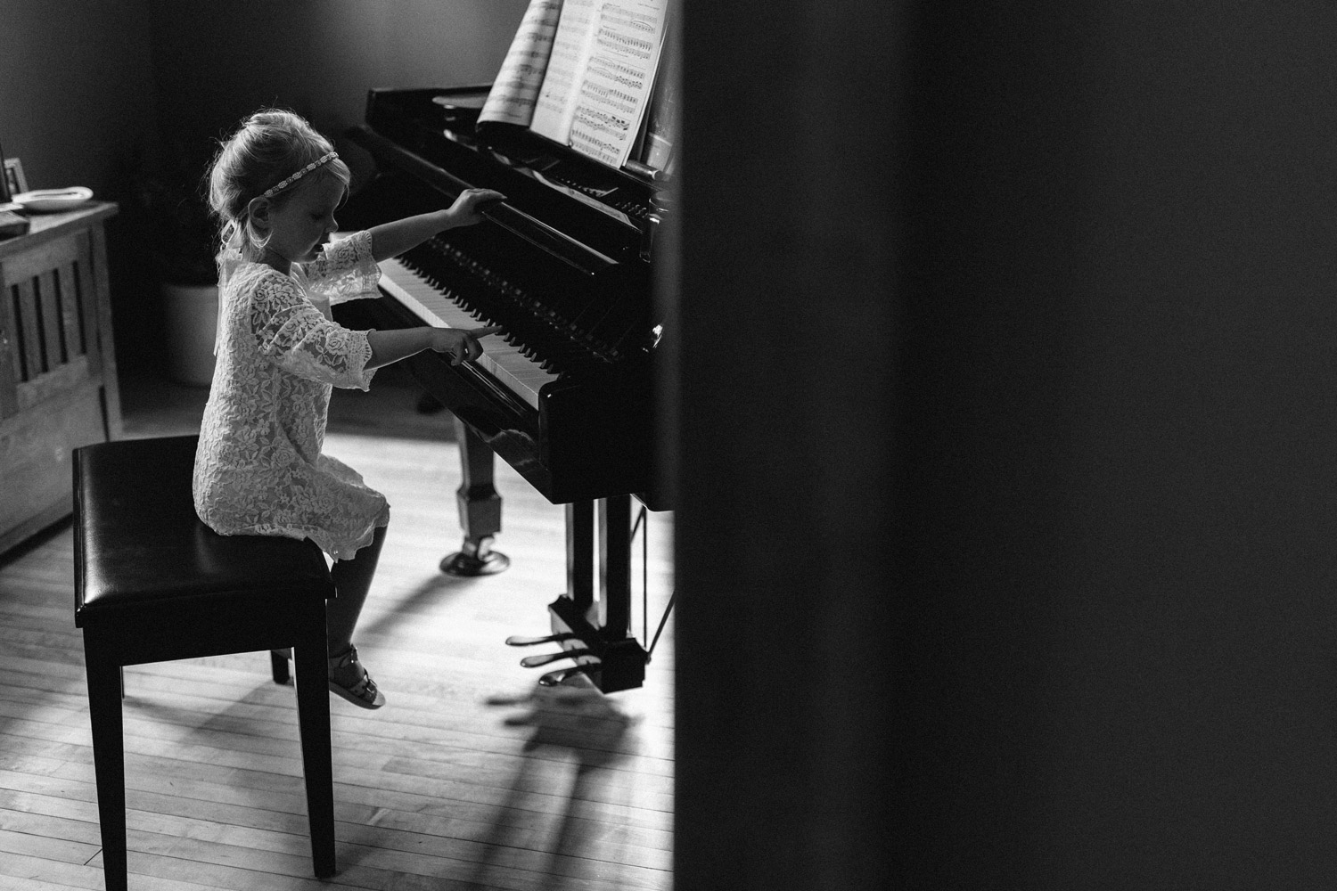 candid of flower girl playing piano by geneoh photography