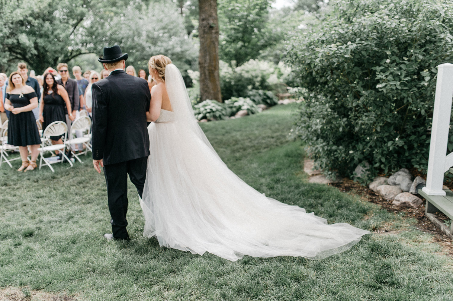 Bride and father walking down the aisle during ceremony at rustic oaks
