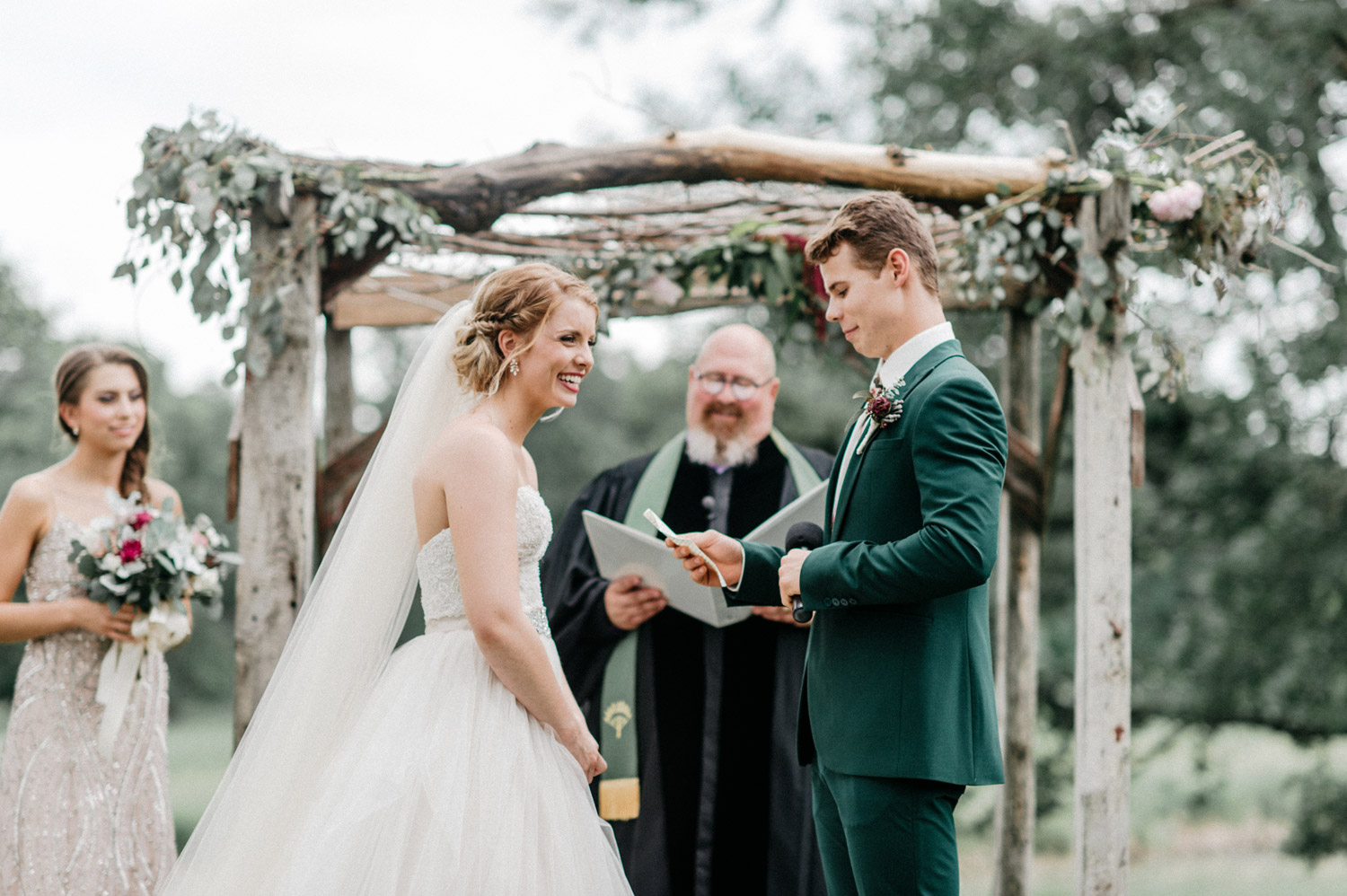 groom reading vows during outdoor ceremony at rustic oaks