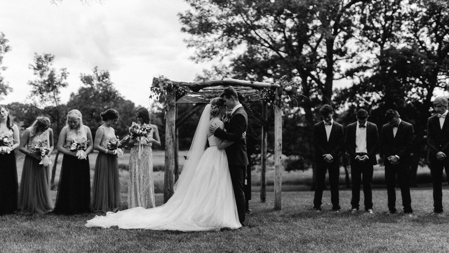 prayer during outdoor ceremony at rustic oaks