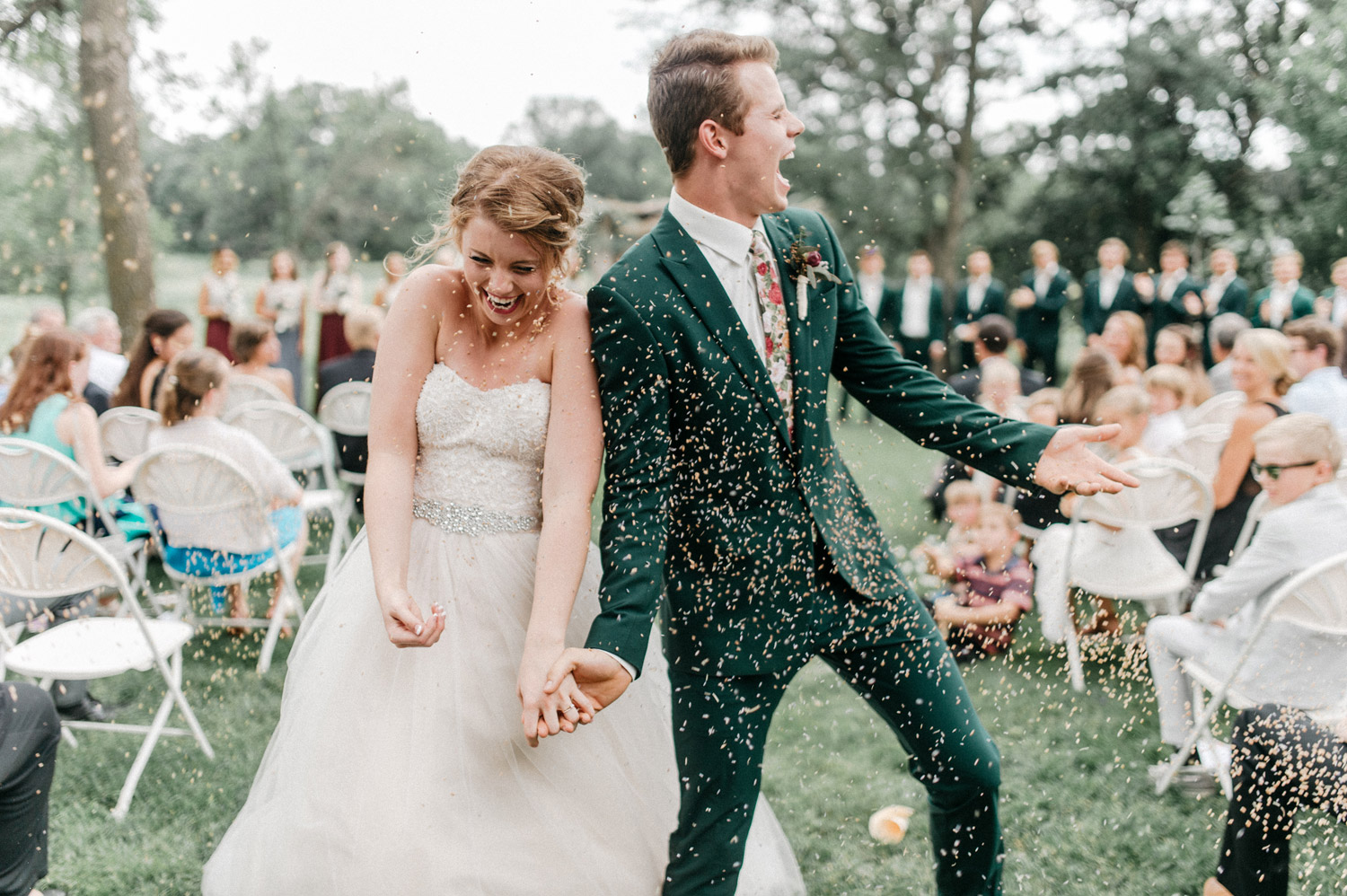 guests throw confetti at bride and groom during ceremony by geneoh photography
