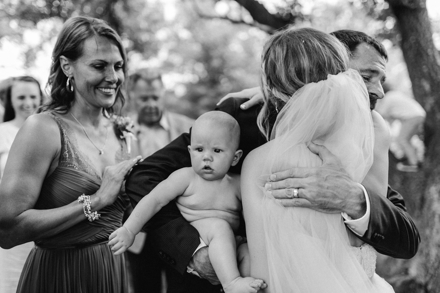 Candid of bride celebrating with family after ceremony at rustic oaks by geneoh photography