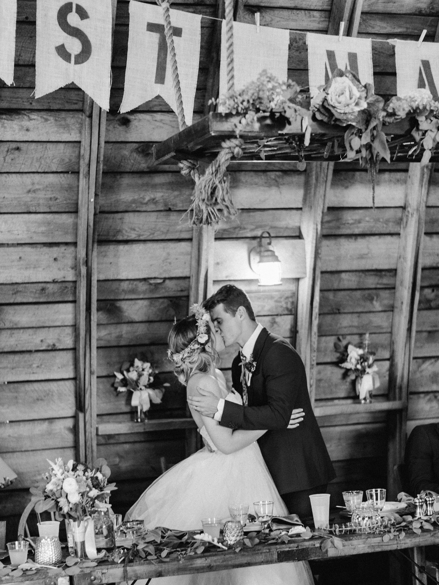 bride and groom kiss during reception at rustic oaks