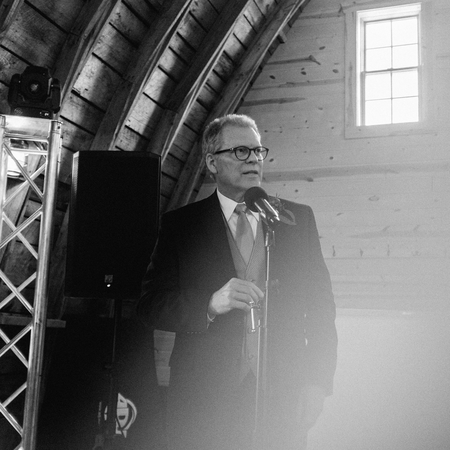 Father of the bride gives speech during reception at rustic oaks