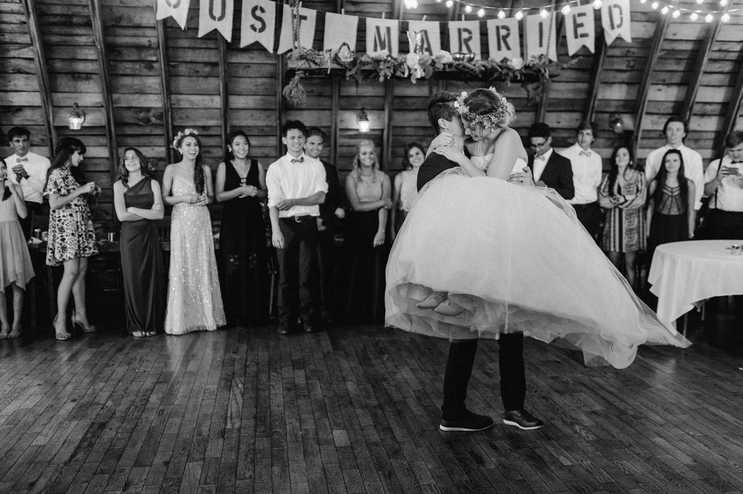 Groom carries bride during first dance at rustic oaks by geneoh