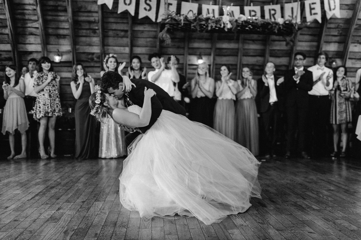 groom dips bride during first dance at rustic oaks by geneoh photography