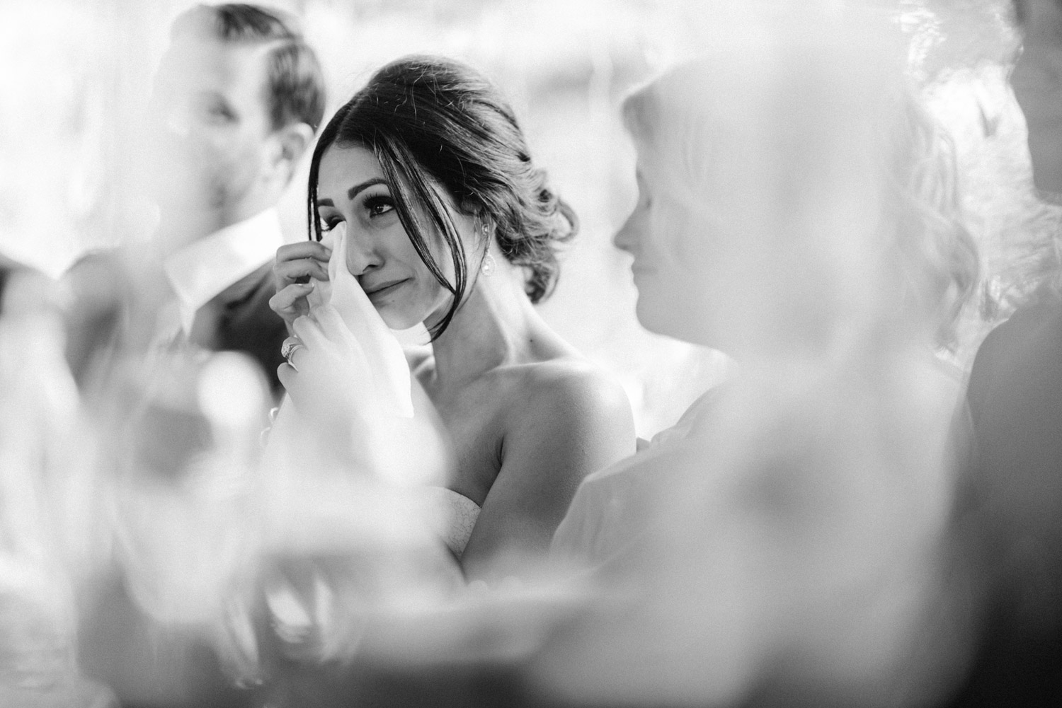 Emotional bride during speeches at reception by geneoh photography