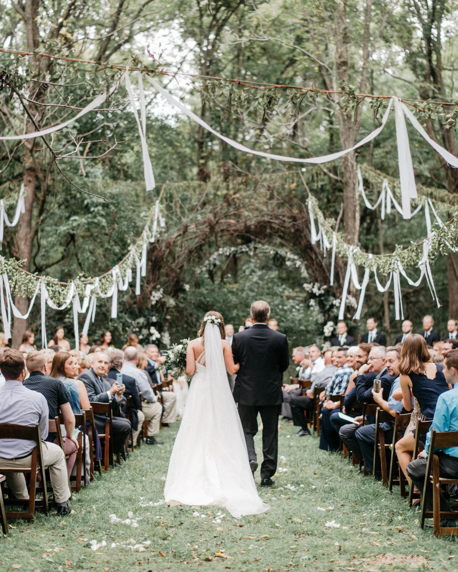 bride and father walk down aisle during outdoor wedding ceremony