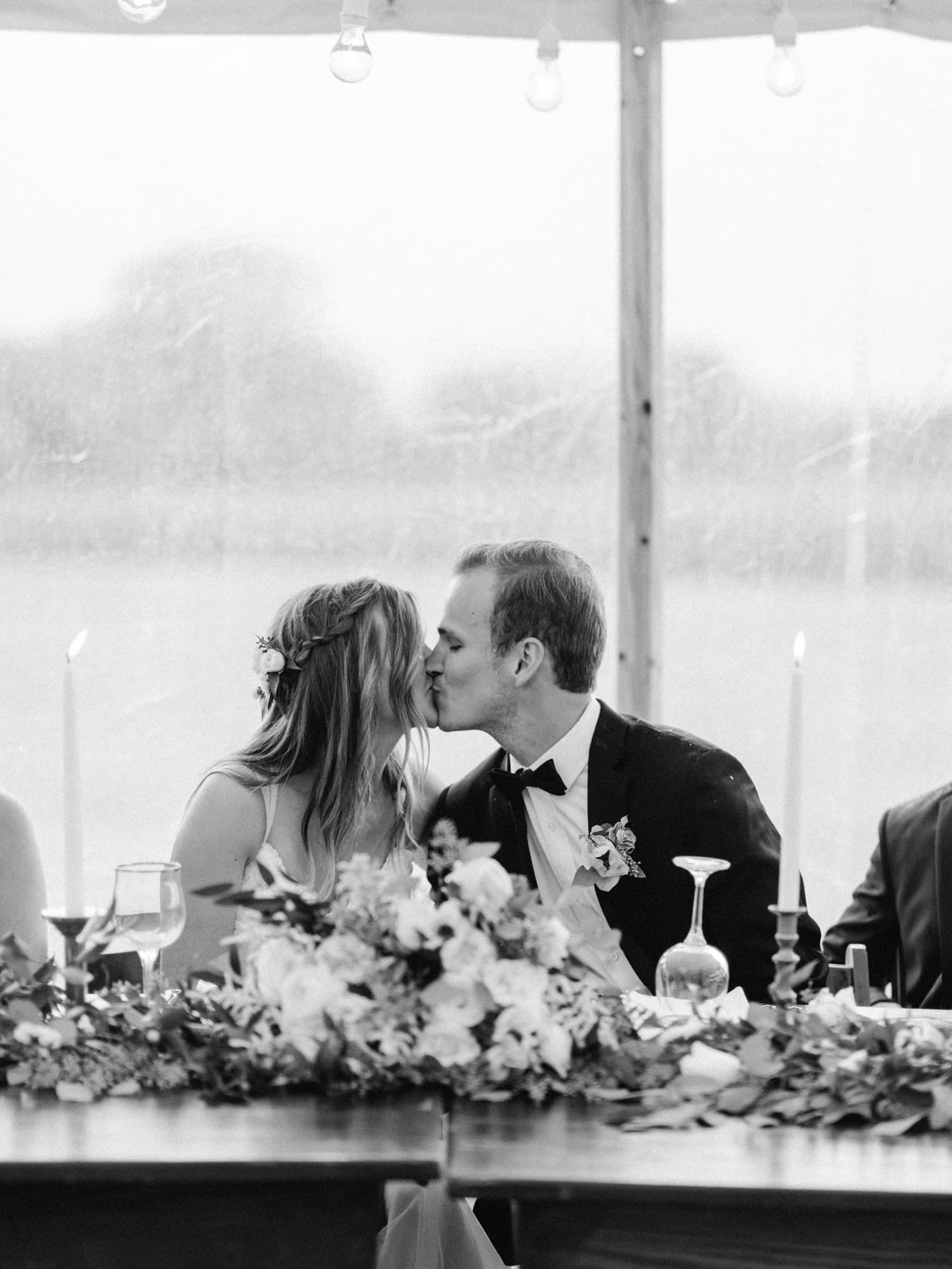 bride and groom kiss during outdoor reception