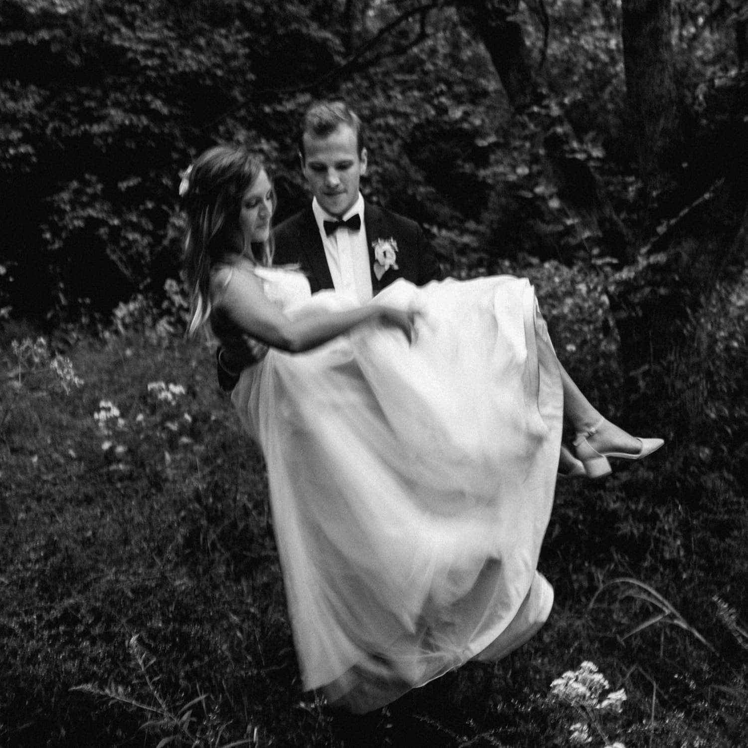groom carries bride during portraits