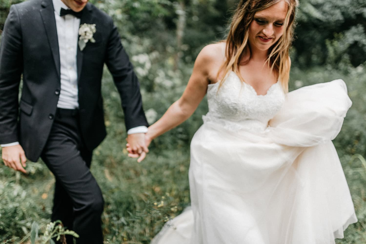 bride and groom walk together during portraits