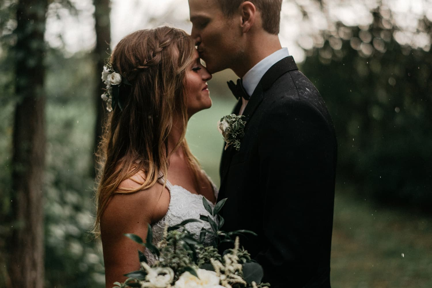 groom kisses bride on the forehead at outdoor wedding