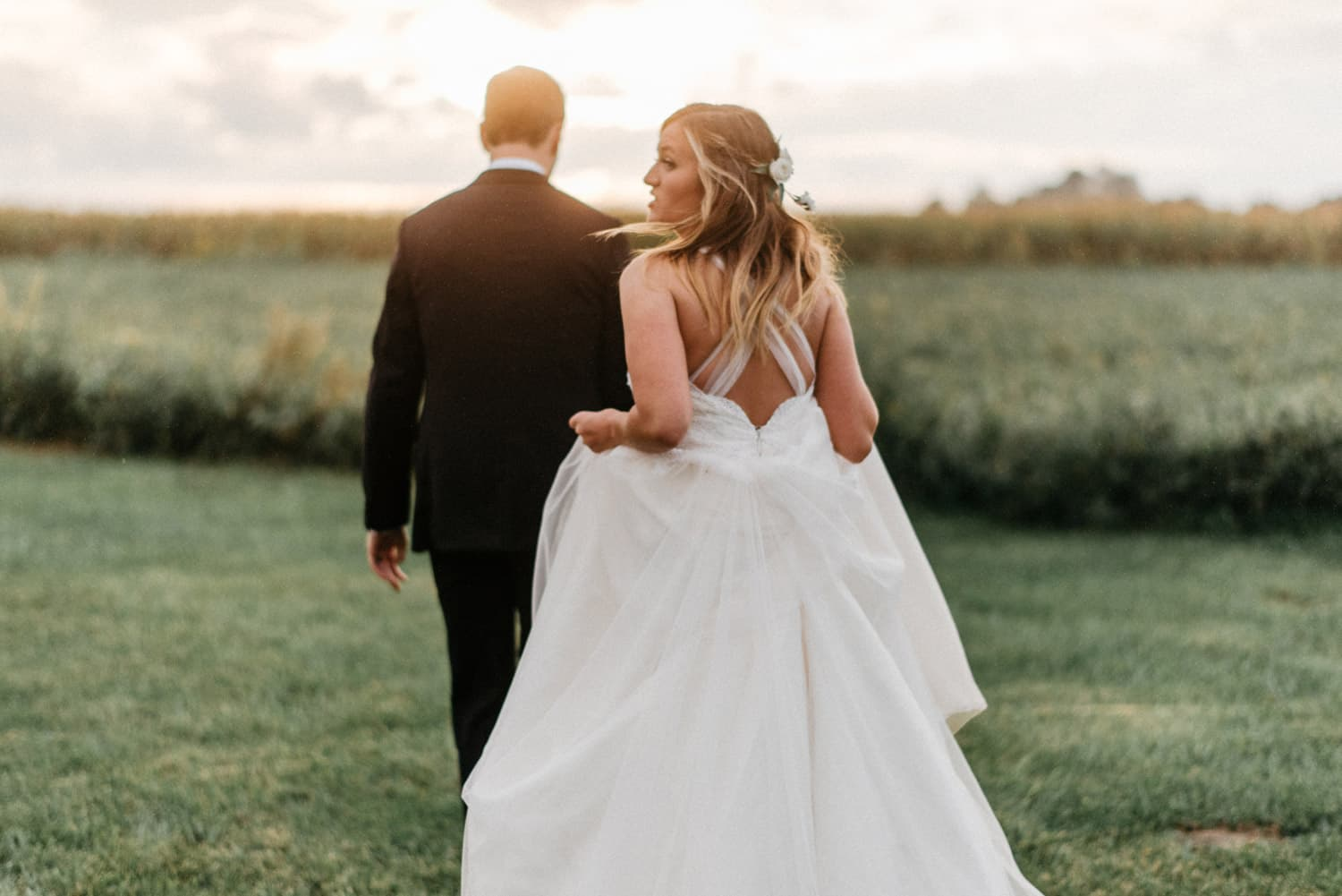 bride and groom walk during sunset